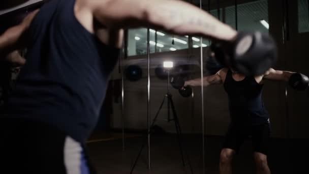 Atletický muž čerpání své svaly v odrazu zrcadla