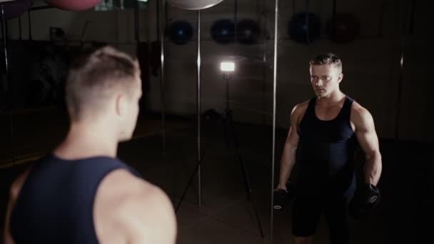 Mužské sportovce čerpání biceps s činka v posilovně na zrcadlo