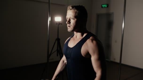 Atletický muž zvedání JEDNORUČKY v tmavých tělocvičně