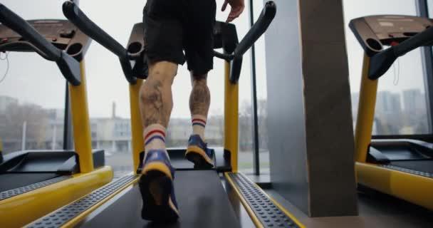 Männerbeine laufen auf einem Laufband im Fitnessstudio, Zeitlupe