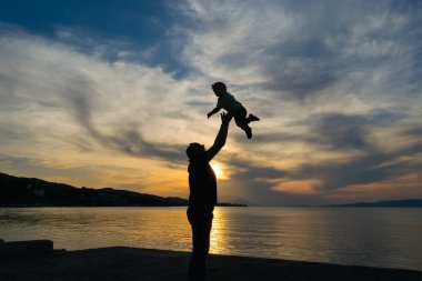 Silhouette of a father and his son against the sunset with a dramatic sky.