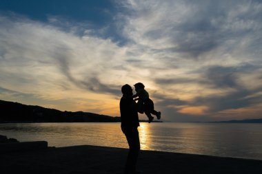 Father and son love silhouette against a dramatic sky.