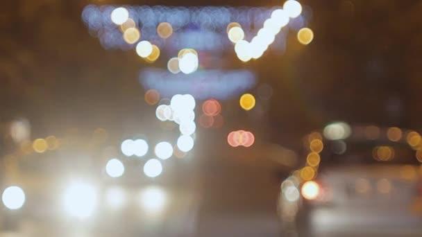 Auta s planoucí reflektory jsou v nočním městě