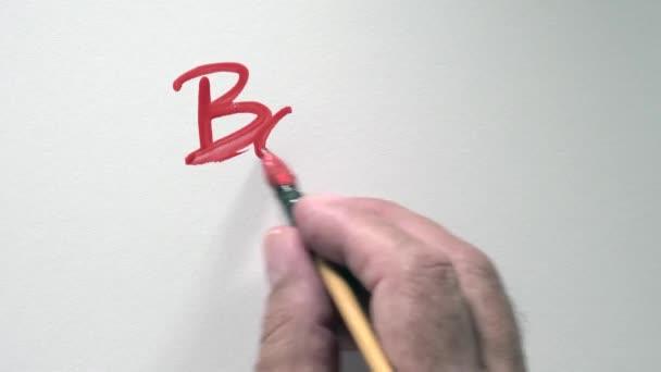 Lidská ruka psát slovo Bonne Annee ve francouzské, s červeným kvaš