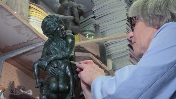 Bildhauer arbeitet an seiner Statue