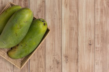Mangoes in basket on wood background