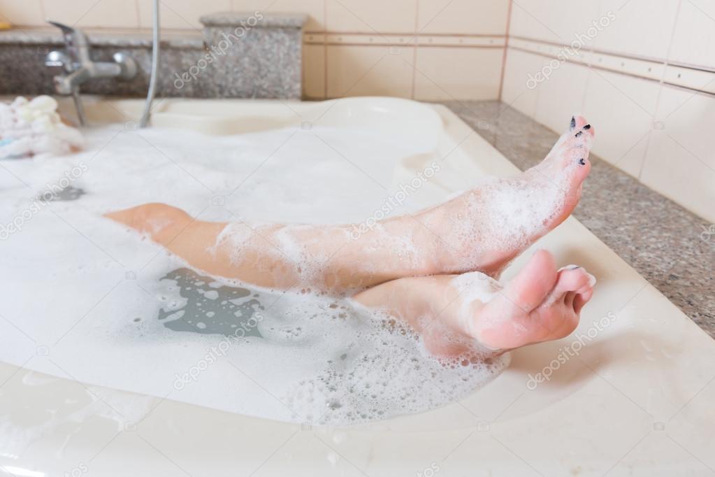 Bella ragazza sotto la doccia e lavare le gambe nella vasca da ...