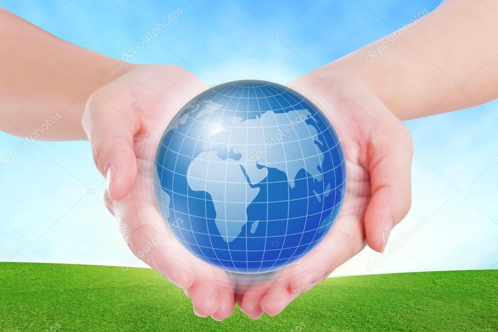 Female hands holding on earth global on grassland.