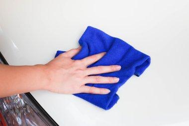 Female hand with microfiber cloth clean white car.