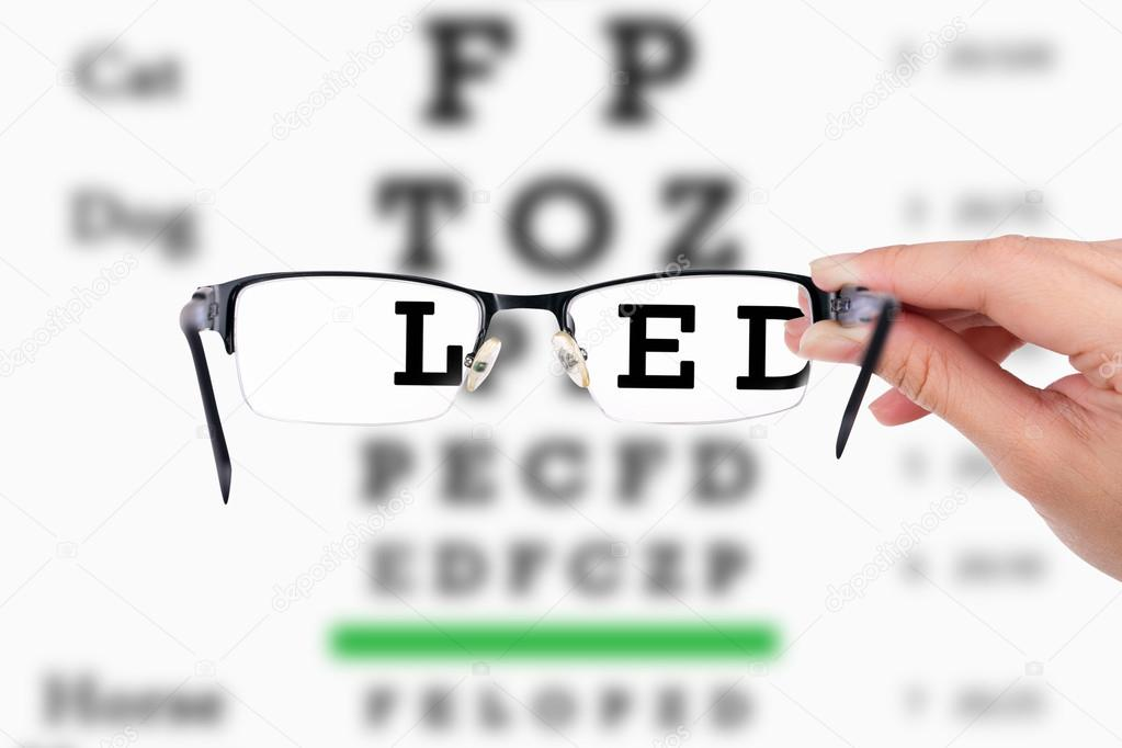 Weiblichen Hand halten Gläser mit Sehkraft Test auf Diagramm-board ...