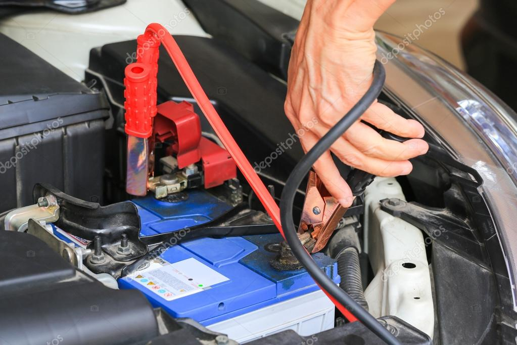 Car mechanic uses battery jumper cables charge a dead