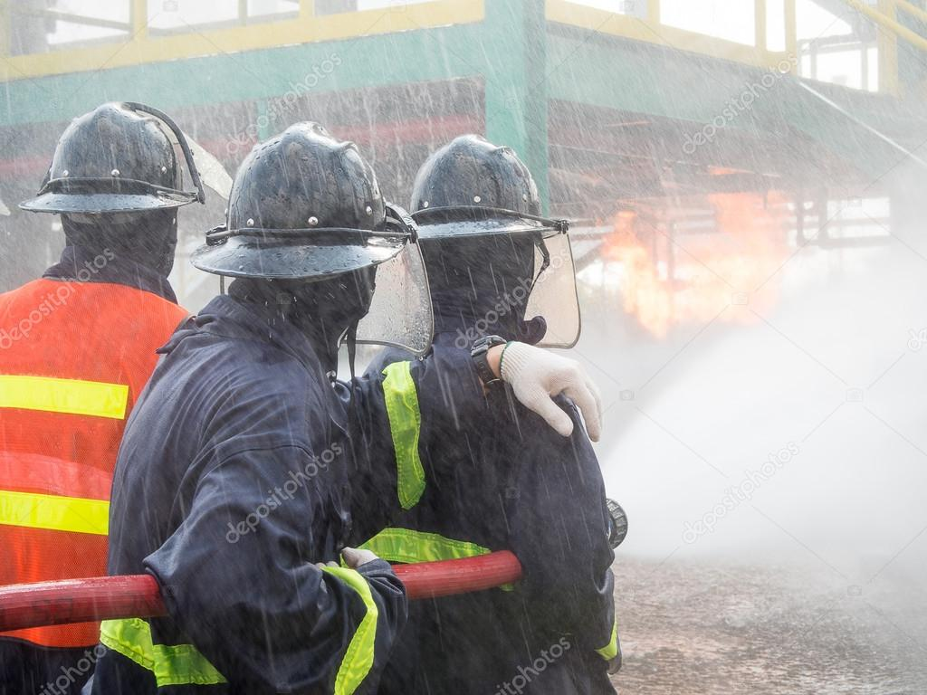 Firefighters fighting fire with pressured water during training exercise. Fire fighter spraying a straight steam into fire off.