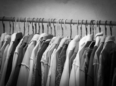 Black and white image of clothes hanging on hanger rack. Choice of fashion clothes on hangers.