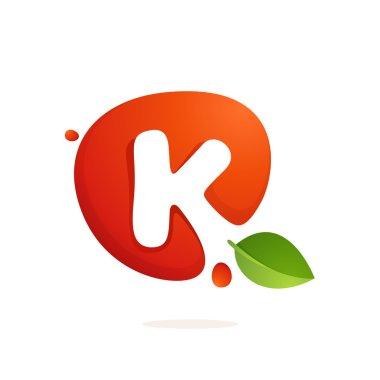 Letter K logo in fresh juice splash with green leaves.