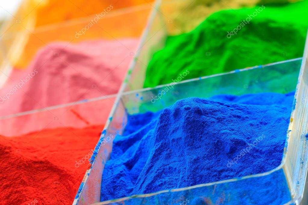 The pile of powder coating in plastic box, on wooden background.