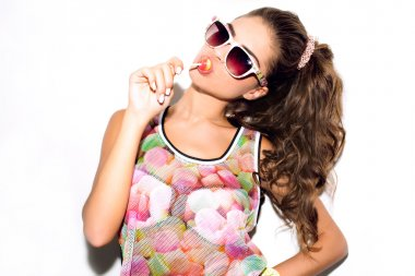 Beauty fashion girl eating lollipop.