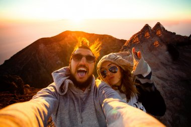 Outdoor portrait of beautiful traveling couple on the top of the mountain, hiker couple, hipster outfit, make selfie of their Asia trip, happy laughing couple, couple in sunglasses, emotional man and tongue girl, crazy selfie, hikers stock vector
