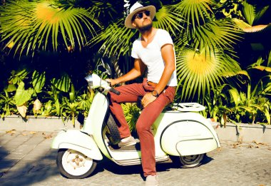 Handsome man ride vintage scooter
