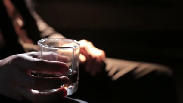 muž v pravé ruce držel sklenku whisky