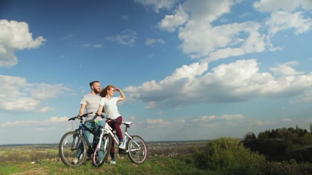Loving couple on bicycles standing on a high hill.