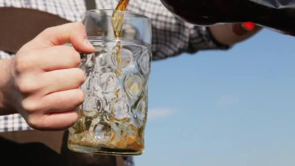 Muž v přírodě nalévá pivo do velké sklenice