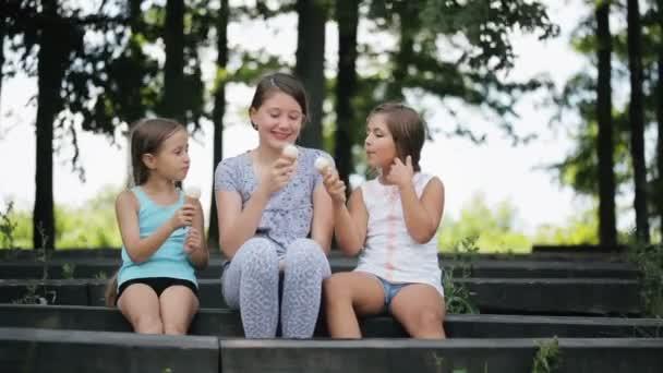 Tři děti, které sedí na lavičce v parku a jíst zmrzlinu