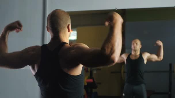 Silná sportovec ukazuje svaly před zrcadlem