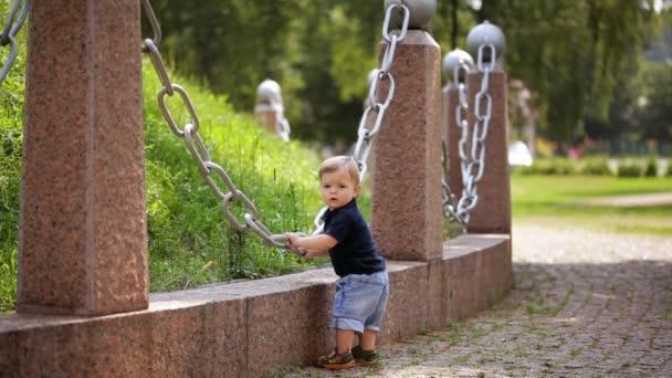 Dítě se učí. Malý chlapec v parku se dotýká velké kovový řetízek.