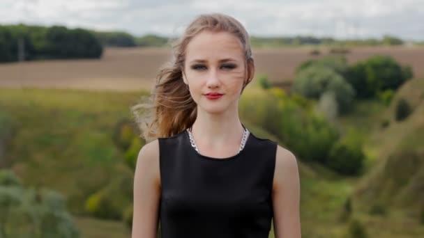 Portrét hezká dívka v černých šatech v přírodě