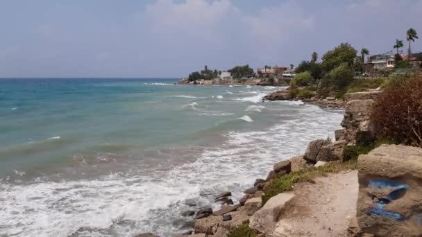 Malebné přímořské městečko Side v Turecku. Prudký útes a vlny narážející na kameny.