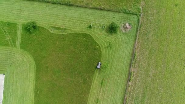 Riding lawn mower in action seen from the sky