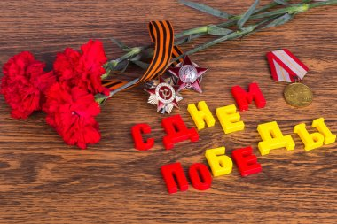 Congratulations on Victory Day: inscription, orders, medals, carnations and georgievskaya ribbon on wooden background