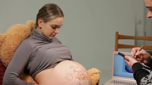 Mladá těhotná žena na břiše zápis