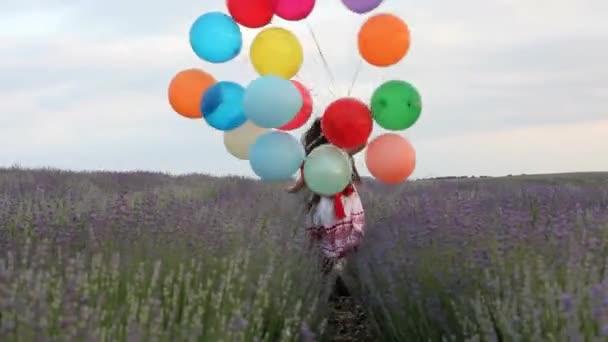 Dívka s balónky běží v levandule