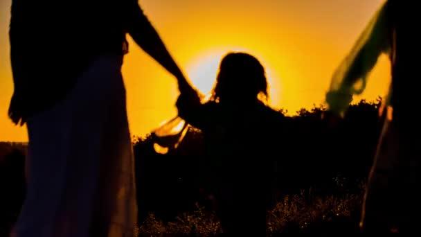 Madre felice con i bambini camminano in natura al tramonto