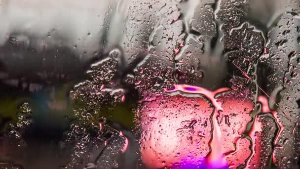 Kapky deště, tekoucí na sklo auta