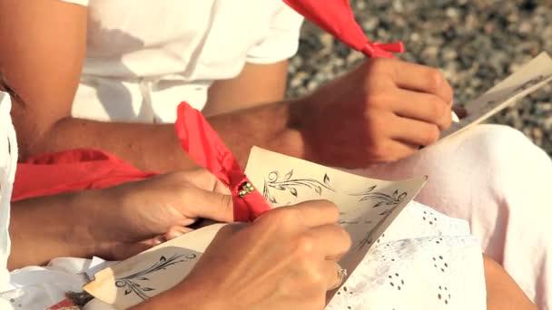 Fiatal férfi és nő-a szerelem romantikus kívánságait ül a strandon írás