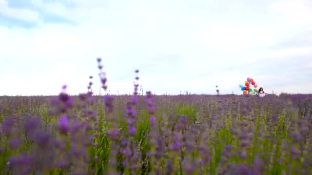 Dítě běží po poli levandule s barevnými kuličkami