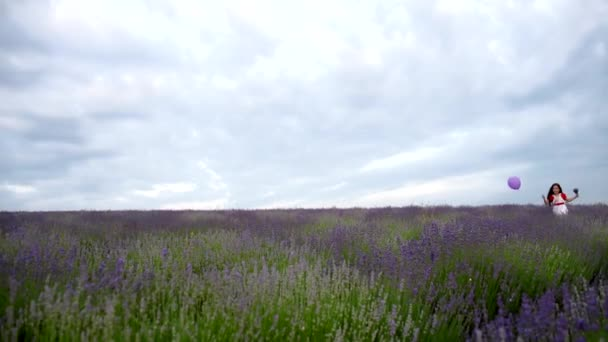 The girl runs with a purple ball in a field of lavender