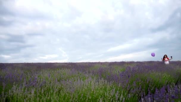 Das Mädchen läuft mit einer lila Kugel in einem Feld von Lavendel