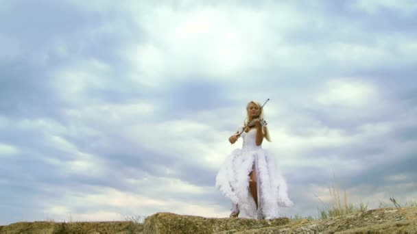 Nádherný houslista v bílých šatech