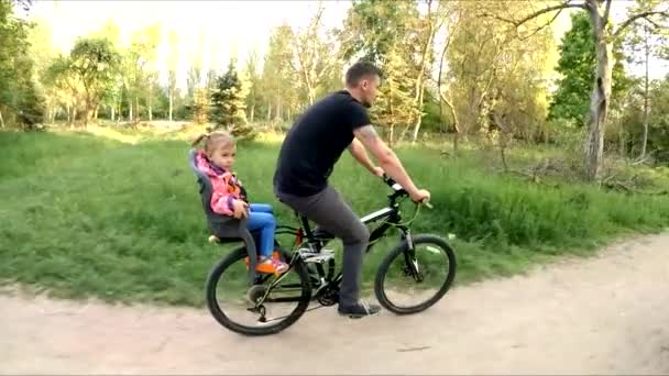 Man With Child On Backseat Riding A Bicycle In Park