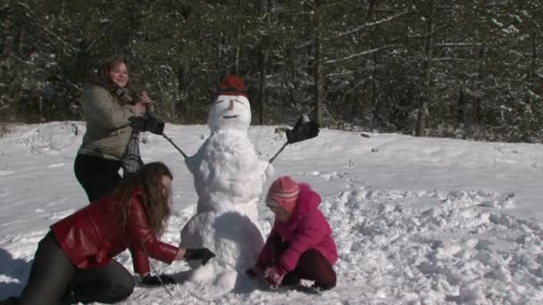 Matka v podřepu s dcerou a sněhulák a úsměv