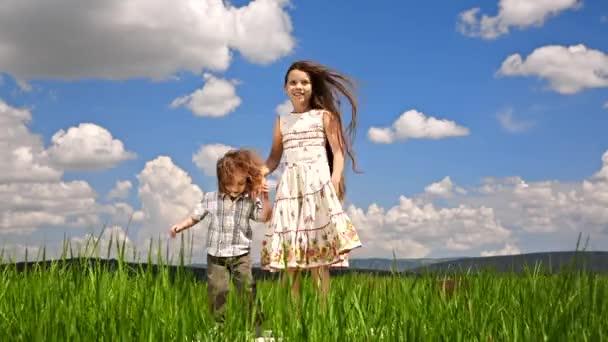 Dívka a chlapec skákání v zelené oblasti