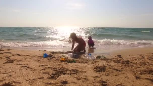 Dvě děti si hrají s pískem na pláži