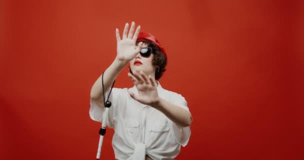 Eine blinde Frau mit Sonnenbrille und Blindenstock versucht nach etwas zu tasten