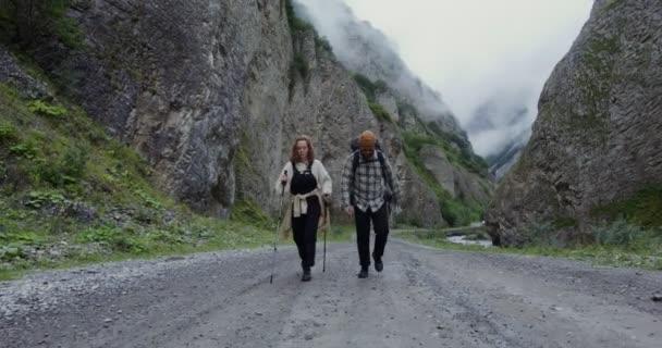 Oroszország, Kaukázus. Egy fiatal turista pár sétál az úton a sziklák között.