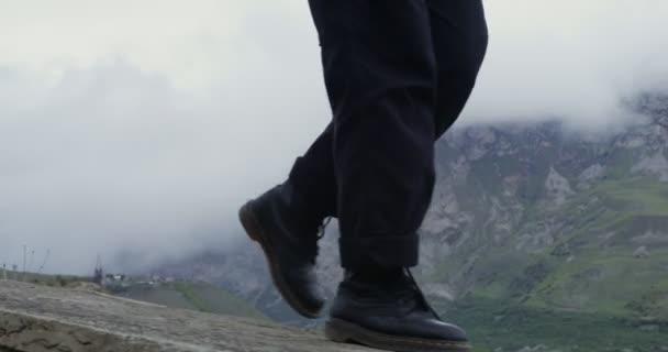 Oroszország, Kaukázus. Közelkép ember sétál végig a mellvéden hegyekkel szemben