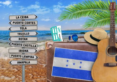 Concept of summer traveling with old suitcase and Honduras town sign