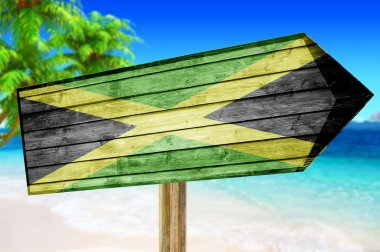 Jamaica flag wooden sign with on a beach background